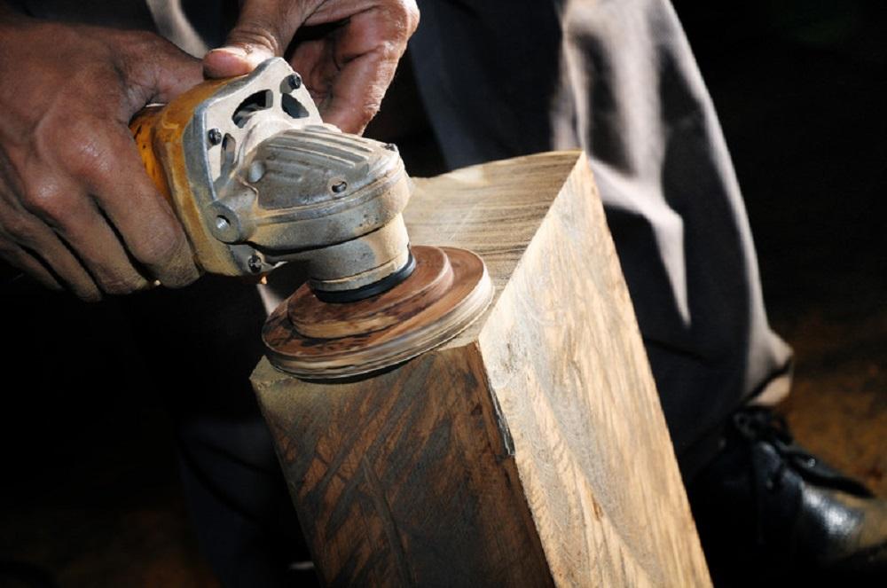 man sanding a wood